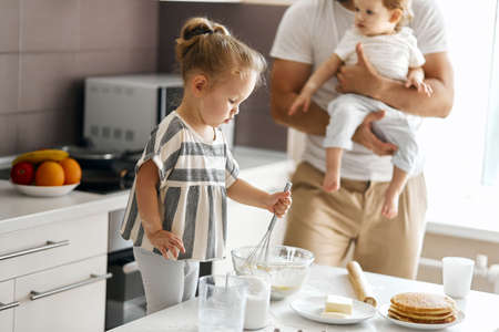 little blonde girl working with whisk while standing on the chair. close up side view photo Stockfoto