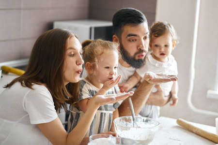young funny family blowing flour in the kitchen, sending kiss, close up side view photo. entertainmnet concept, lifestyle