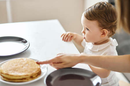 woman pointing to pancakes, asking the kid to taste them. close up cropped side view photo 写真素材