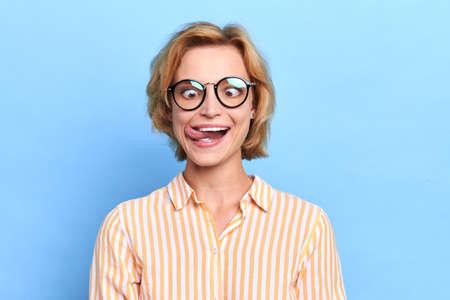 Lustige blonde Frau mit Brille, die Grimasse macht, Mädchen, das Spaß im Studio mit blauer Wand hat. Nahaufnahme Porträt, Unterhaltung