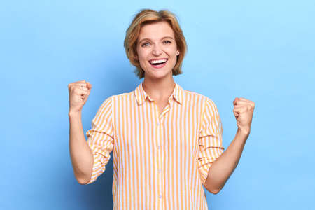 winning successful young girl rejoicing her victory, success. Positive human emotion facial expressions. Life achievement concept, close up portrait, isolated blue background, studio shot well done Imagens