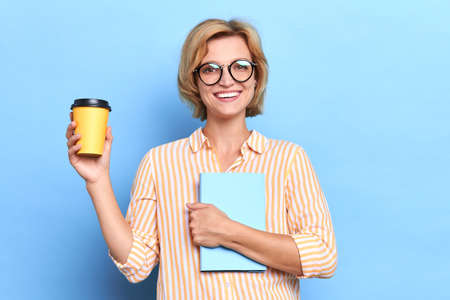 close up portrait of a smiling casual woman holding copy book and takeaway coffee cup isolated over blue background, free time, spare time, lifestyle. close up portrait Imagens