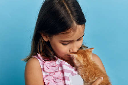 little kid giving kiss to her lovely cat, close up photo. friendship concept, isolated blue background