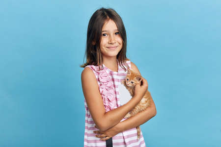 cheerful positive little kid taakes care of her orange kitten, close up portrait, isolated blue background, positive feeling and emotion