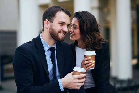 cheerful smiling pleasant woman and man in elegant fashion suits rejoicing at free time outdoors, warm feeling, emotion , man and woman fall in love. I love you,woman whispering something to boyfriend