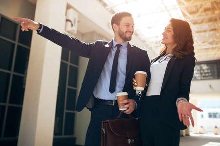 Hombre barbudo feliz mostrando con un dedo en el edificio invitando a la mujer a cooperar, bienvenida, foto de cerca