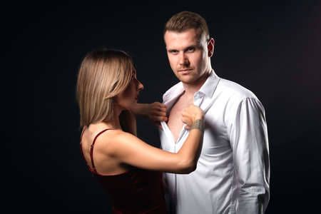 blonde woman and man preparing for a passionate night, close up portrait, isolated black background, studio shot