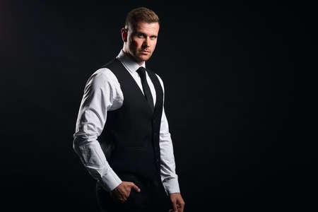 hombre guapo elegante con una mano es bolsillo mirando a la cámara. retrato de cerca, fondo negro aislado, tiro del estudio. Copie el espacio.