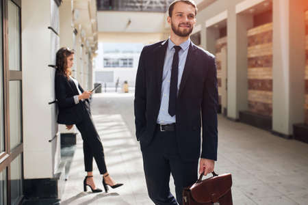 happy ambitious businessman leaving the office building, elegant woman in stylish suit working with a tablet leaning on the wall. close up photo