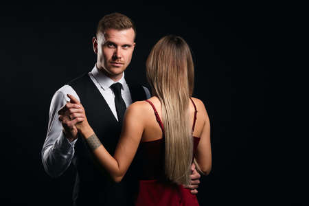 stylish fashion man holding his ladys hand looking at the camera. isolated black background, studio shot. copy space