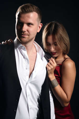 romantic blonde woman in elegant red dress standing behind her boyfriend taking off his shirt. close up portrait, isolated black background, studio shot.