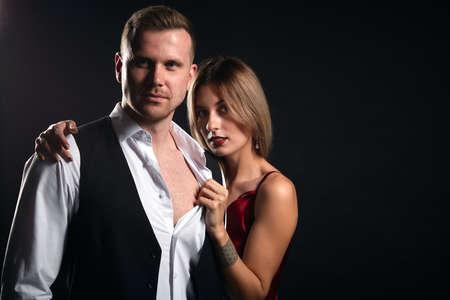 handsome strong man in elegant shirt nad vest standing with his girlfriend in the dark studio, close up portrait, relationship. close up portrait, studio shot