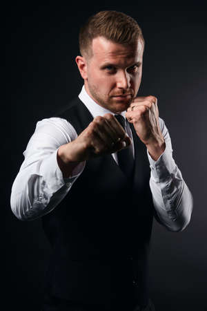 young serious businessman standing with clenched fists preparing to kick, close up portrait, isolated black background, studio shot, man fighting with competitor