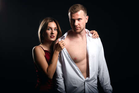 young woman in elegant red dress standing behind the man with half naked body. close up portrait, isolated black background, studio shot.