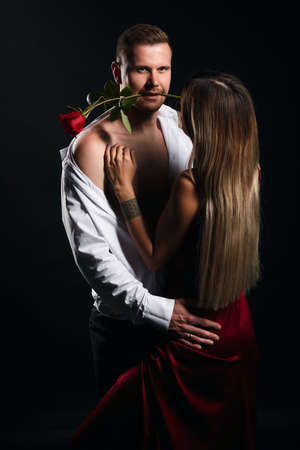 A man with half naked body got a kiss trace on the cheek. Close-up photo. isolated black background, studio shot.woman cheking her husbands face,jealousy