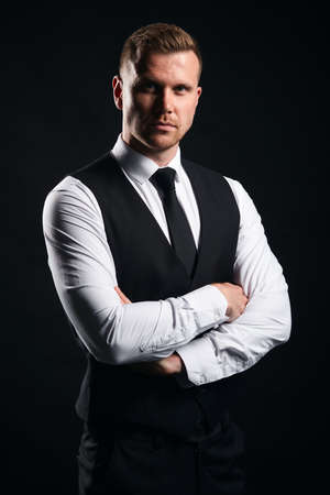 Confident young strong muscular bodyguard standing with crossed arms, isolated black background, studio shot.