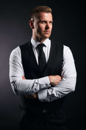 serious pleasant strong man in fashion shirt, vest and tie crossing his arms looking aside, close up isolated black backgrround, studio shot.