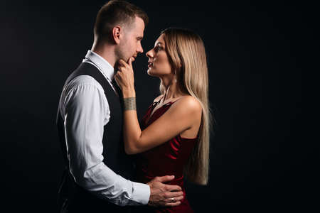 blonde attractive woman looking at her boyfriend, touching his chin, telling him secret, close up side view photo. isolated black background, warm , tender feeling