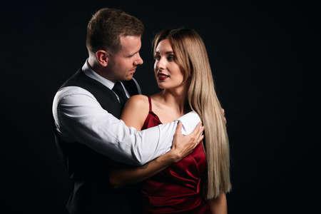 handsome smart man embracing his lover warmly. close up portrait, isolated black backgroud, studio shot