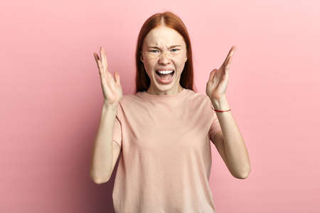angry frustrated unhappy woman with freckles shouting at somebody. I hate you. girl has a fight, argument with boyfriend, negative feeling and emotion, reaction.isolated pink background, studio shot