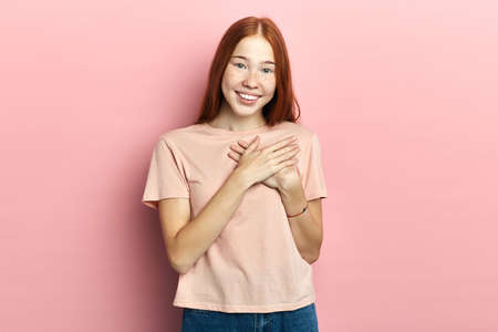 Kind friendly smiling young good looking woman keeps palms on heart, being postive and kind hearted, expresses good feelings poses against pink studio background.thank you, I appreciate it Stok Fotoğraf