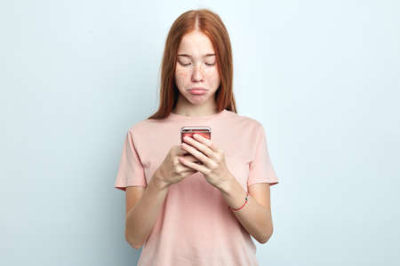 displeased gloomy offended woman using smartphone isolated on a white background, girl received message with sad unpleasant consept. close up portrait, negative feeling and emotion, depression Stock fotó