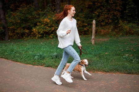happy girl with ponytail goes in for sport with her pet, full length photo. weekend, wellness Stock Photo