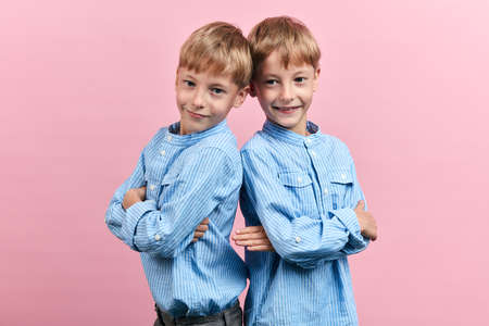 happy positive handsome brothers in blue striped stylish shirts standing back to back with crossed arms, happiness, childhood, isolated pink background, studio shot, relationship Stock fotó