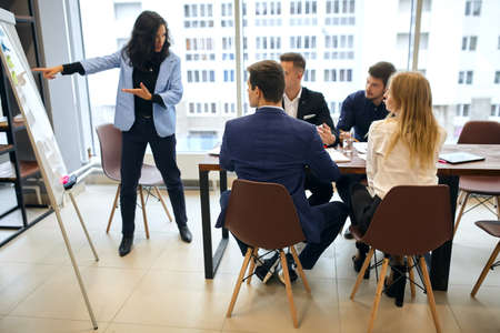 clever brunette woman standing and presenting graph on flipchart during business meeting, businessmen and businesswomen sitting at conference table at the same time. lifestile, job, profession