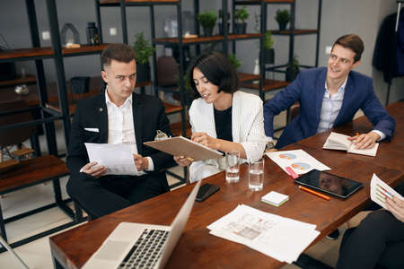 brunette woman holding folder in hands making notes explaining something to colleague while he is sitting at desk with serious expression and looking at camera Zdjęcie Seryjne - 132243351