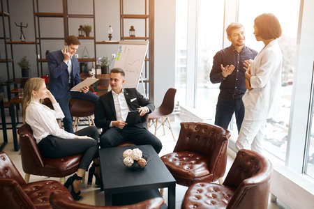 young relaxed positive people in formal stylish clothes having a rest at workplace, busy atmosphere in the office room