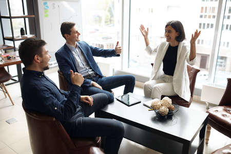 Two cheerful handsome businessmen showing thumb up to their female colleague who is sitting at the table with outstretched arms, our congratulations, happiness.positive feeling and emotion, promotion Zdjęcie Seryjne - 132243325