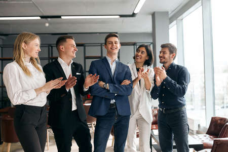 Business team celebrating their co-woker with promotion, happiness, business people congratulating their new boss who is standing with crossed arms . positive feeling and emotion Zdjęcie Seryjne - 132243167