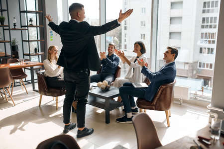 Photo of successful businessman raising his arms expressing positive feeling and emotion, back view photo. happiness, celebration