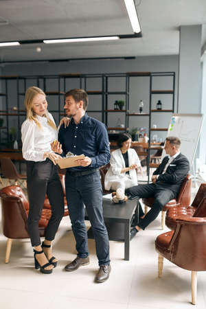 young handsome man showing document to blonde woman asking to give him a helping hand, full length photo. consultation, conversation Zdjęcie Seryjne - 132243359