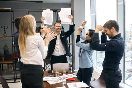 talented successful creative handsome leader showng signed contracts to colleagues. company bought new stock positive feeling and emotion, team celebrating successful project, we done it. we did it Zdjęcie Seryjne - 132243118