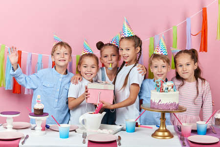 friendly smiling children holding a box with gift posing to the camera during the party, happiness, isolated pink background, studio shot. friendship