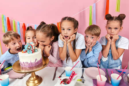 children wth fists under their chind standing around the cake waiting for their portion, isolated pink background, studio shot
