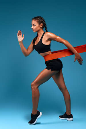 motivated awesome slim woman exercising fitness resistance bands, full length side view photo. isolated blue background, studio shot. lifestyle Stock Photo