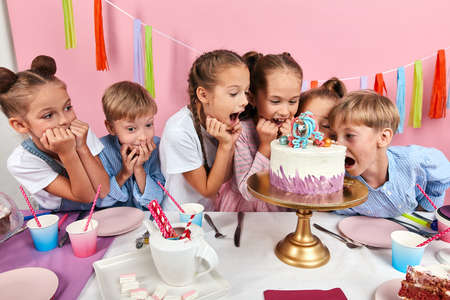 children enjoying creative decoration of dessert, close up photo.isolated pink background, studio shot