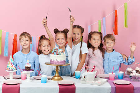 happy little guests are celebrating party in the kindergardern. isolated pink background, studio shot