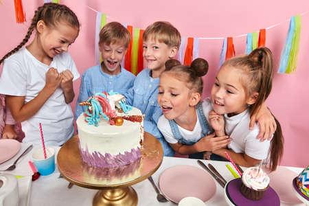 Happy group of children rejoicing at the look of birthday cake, kids going to taste dessert. studio shot