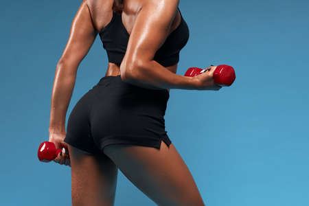 close up cropped photo. woman with butt working out with red dumbbells. back view photo. isolated blue background, studio shot Reklamní fotografie