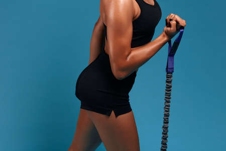 young strong sportswoman pumping her muscles, isolated blue background, studio shot.strength training. hobby, interest, lifestyle