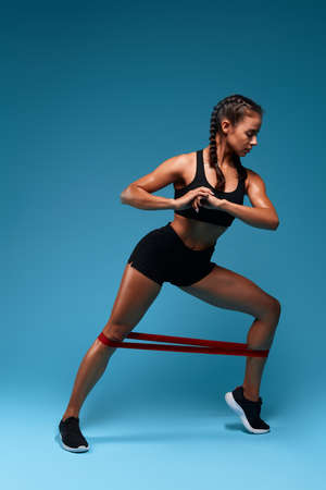 serious girl using expander to perform lunge, full ength photo. isolated blue background, studio shot.free time, spare time, lifestyle