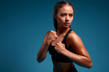strong motivated serious woman with clenched fist and perfect abdomen ging to box. girl protecting herself. protection, martial art. strength training. hobby, interest, lifestyle, spare time