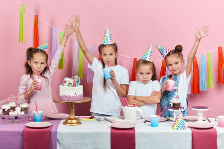 unhappy depressed sad little girl standing with crossed arms , her friends celebrating birthday. isolated pink background, facial expression