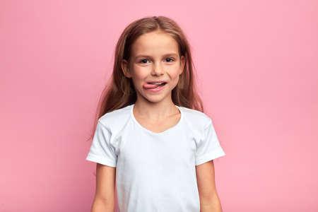 niña loca divertida muestra su lengua. retrato de cerca, fondo rosa aislado. tiro del estudio. Foto de archivo