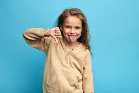 funny crazy girl gesturing thumbs down and sticking out her tongue isolated over blue background. close up portrait, isolated blue background, child making faces, kid having fyn, teasing somebody