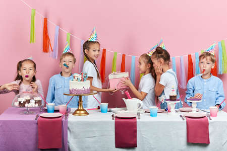 children giving gifts at birthday party, pleasant moments, time, happiness, studio shot, pik background, happy childhood